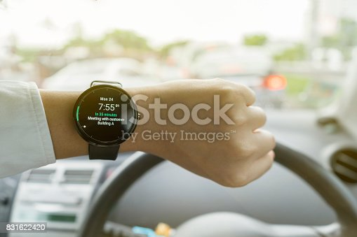 istock Close up of man in car on road watching smartwatch and using application navigation map to destination 831622420