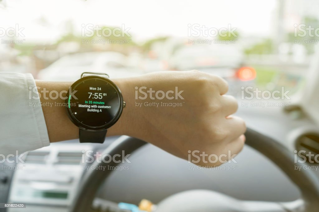 Close up of man in car on road watching smartwatch and using application navigation map to destination stock photo