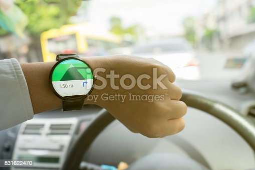 istock Close up of man in car on road watching smartwatch and using application navigation map to destination 831622470