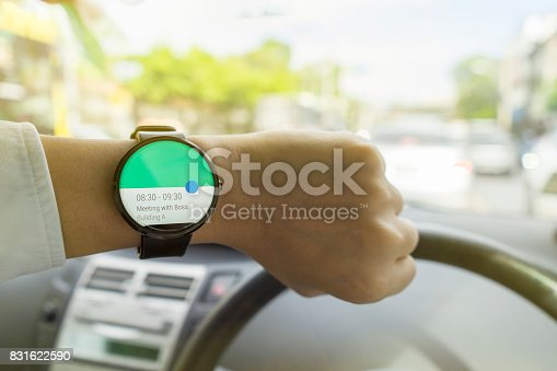 istock Close up of man in car on road watching smartwatch and using application navigation map to destination 831622590
