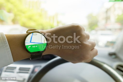 istock Close up of man in car on road watching smartwatch and using application navigation map to destination 831622648