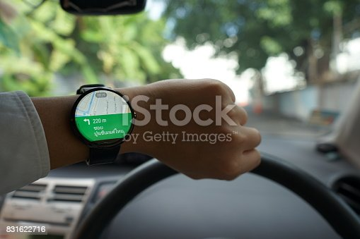 istock Close up of man in car on road watching smartwatch and using application navigation map to destination 831622716