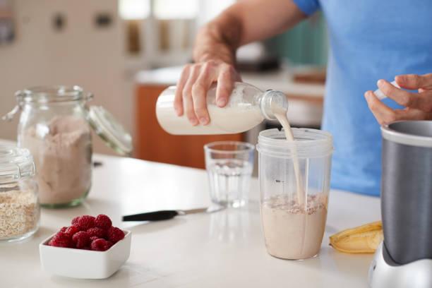 Nahaufnahme des Menschen macht Protein Shake nach dem Training zu Hause – Foto