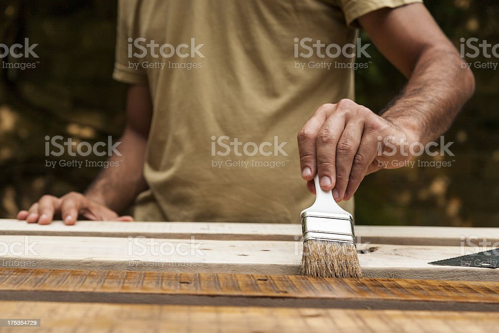 Close up of  man painting a fence stock photo