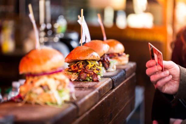 nahaufnahme des menschen zahlen für frische flamme gegrillte burger in einer reihe am lebensmittelmarkt mit kredit- oder debitkarte angezeigt - streetfood stock-fotos und bilder