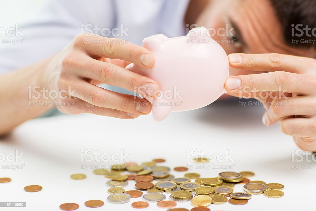 close up of man pouring coins from piggy bank stock photo
