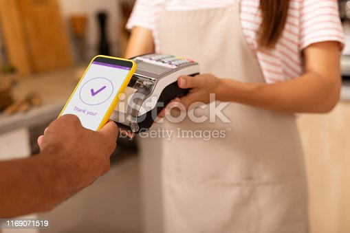 Contactless payment. Close up of man processing contactless payment in cafeteria after drinking coffee