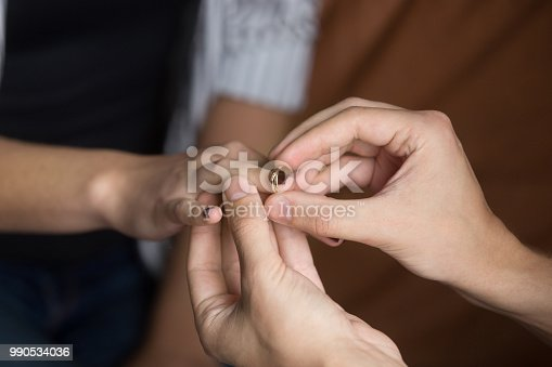 Close up of man putting wedding ring on woman finger making marriage proposal to beloved, boyfriend proposing to girlfriend, lovers couple getting married or engaged. Concept of engagement