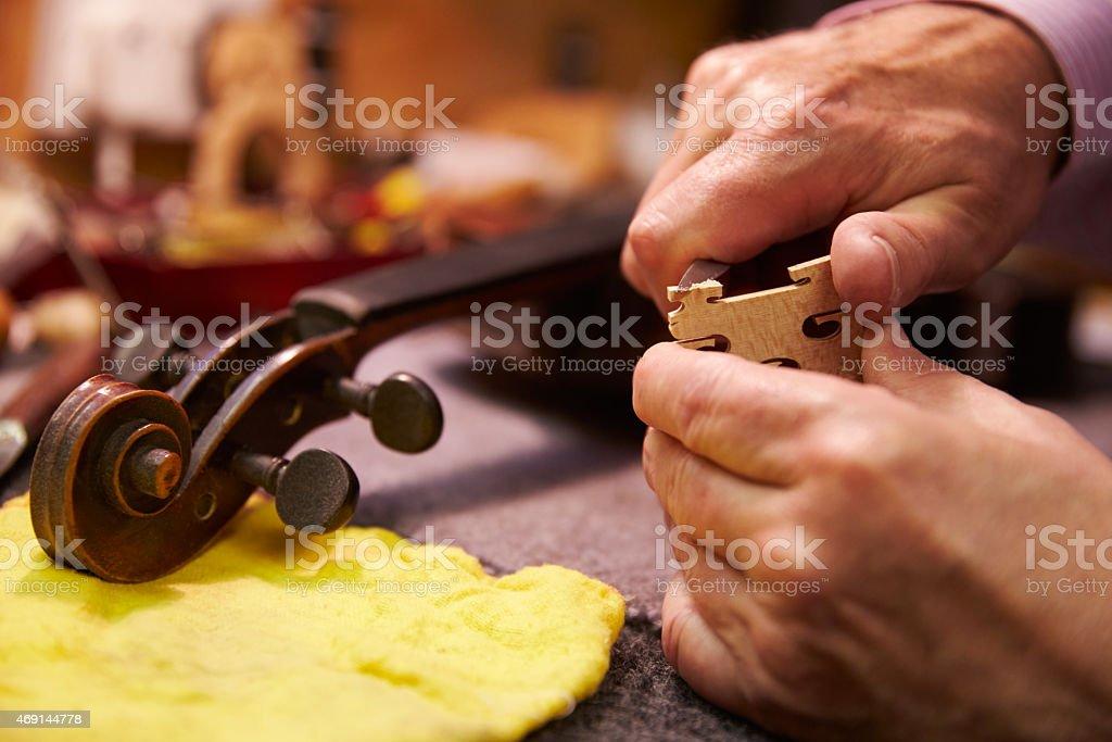 Close Up Of Man Restoring Violin In Workshop stock photo