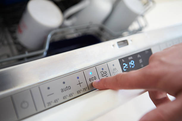 Close Up Of Man Setting Economy Cycle On Dishwasher Close Up Of Man Setting Economy Cycle On Dishwasher dishwasher stock pictures, royalty-free photos & images