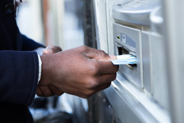 Close up of man taking cash from ATM with credit card. stock photo
