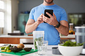 istock Close Up Of Man Using Fitness Tracker To Count Calories For Post Workout Juice Drink He Is Making 1162988619