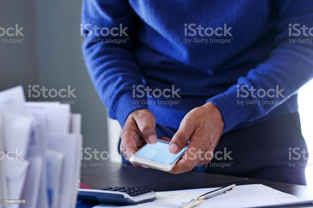 Close Up Of Man Using Mobile Phone To Pay His Bills stock photo