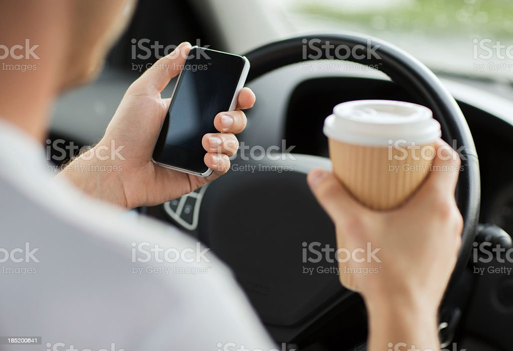 close up of man using phone while driving the car stock photo