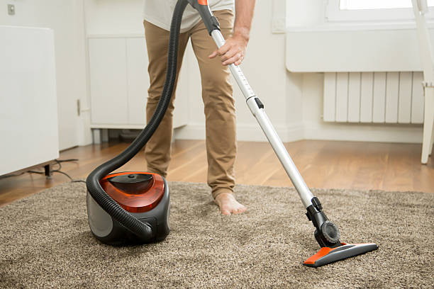 close up of man vacuum cleaning the carpet - tapijtveger stockfoto's en -beelden