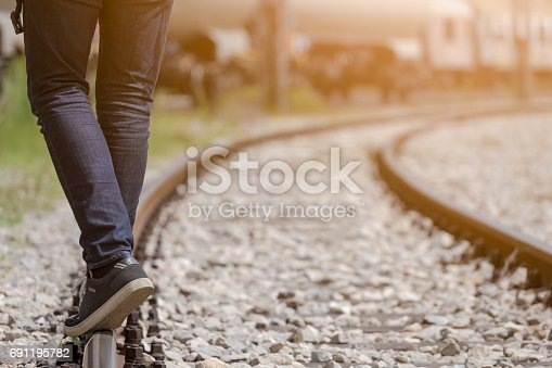 Close up of male legs waking on the railroad