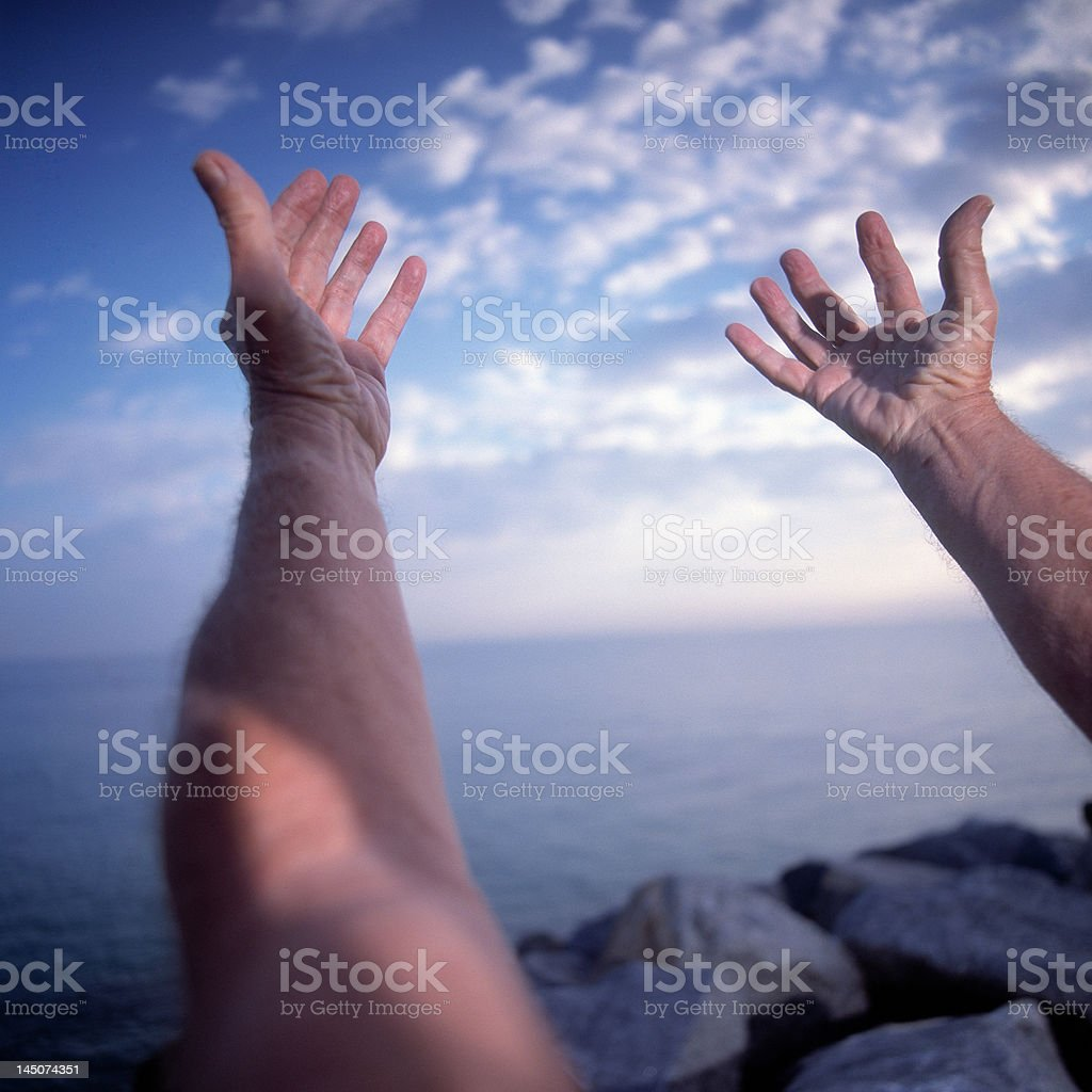 Close up of man with arms stretched in yoga pose by the ocean stock photo
