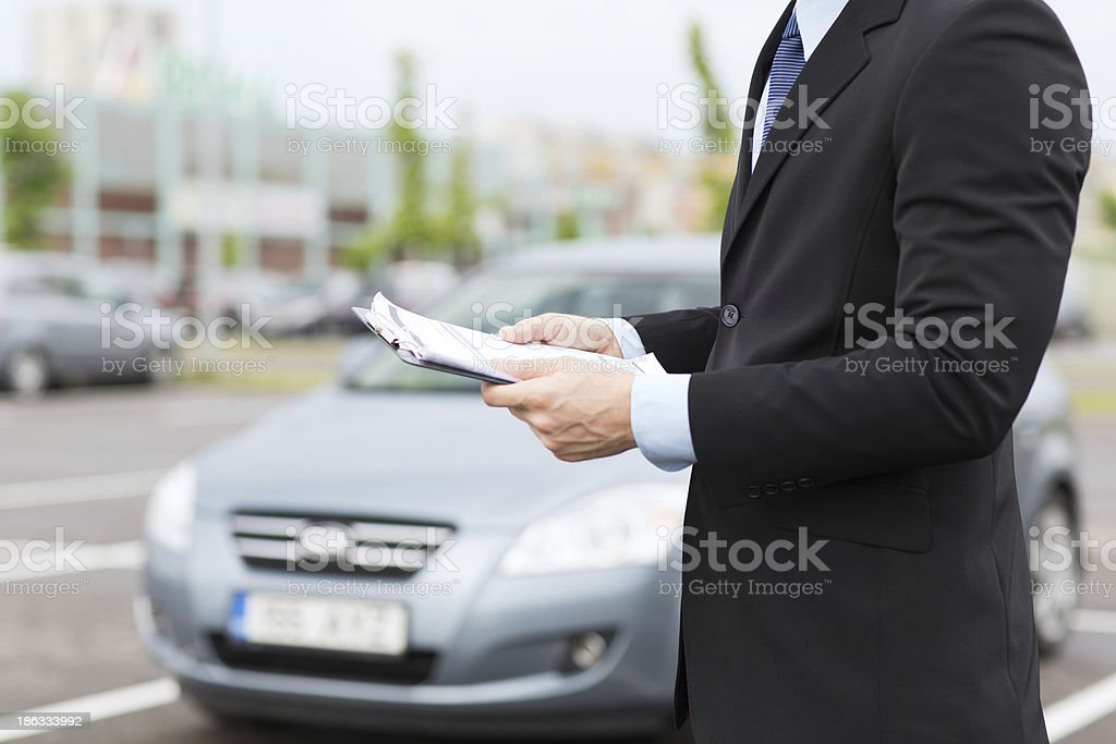close up of man with car documents outside stock photo