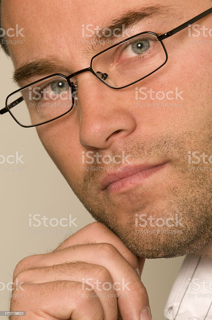 Close up of man with glasses with hand on his chin. royalty-free stock photo