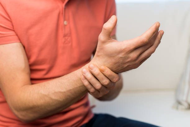 close up of man with  pain in hand at home stock photo