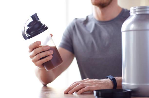 Nahaufnahme des Menschen mit Proteinshake Flasche und Glas – Foto