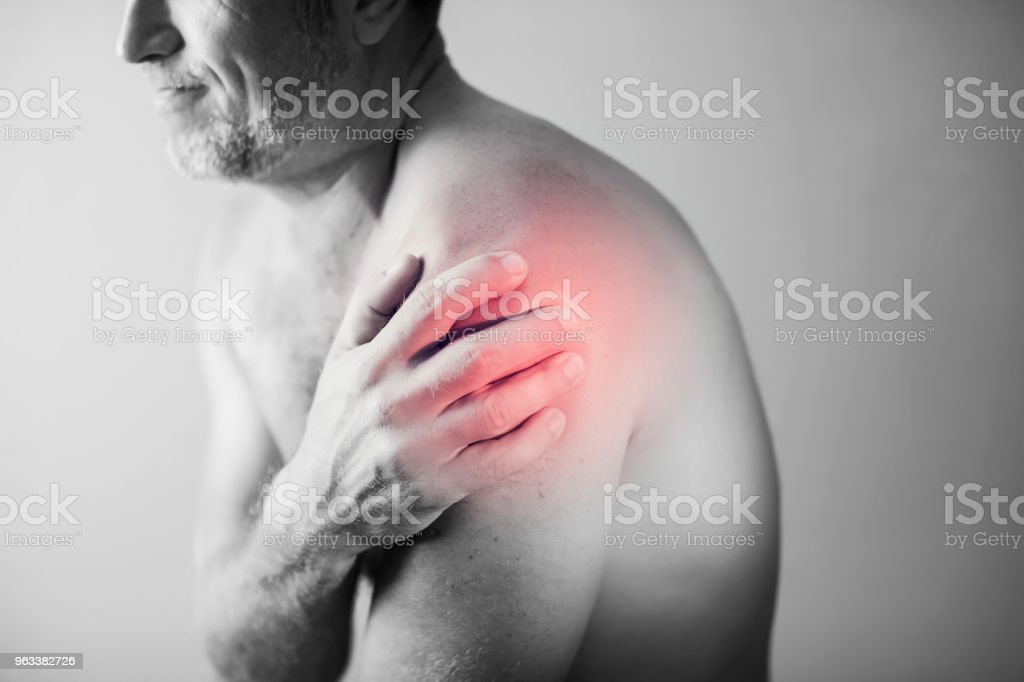Close up of Man with shoulder pain or neck pain on white background,Health concept - Zbiór zdjęć royalty-free (Anatomia człowieka)