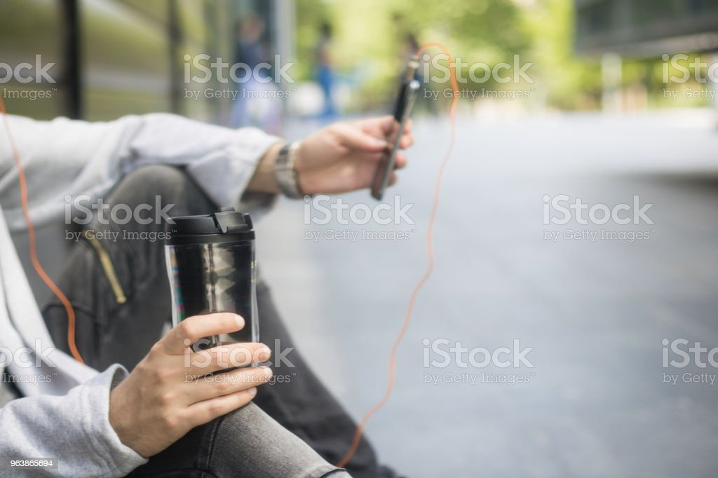 Close up of man with takeaway coffee in the city. - Royalty-free Adult Stock Photo