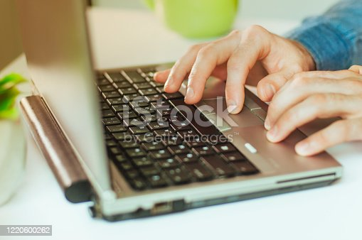 Close up of man working on the notebook. Work or learning online from home during quarantine concept. Selective focus.