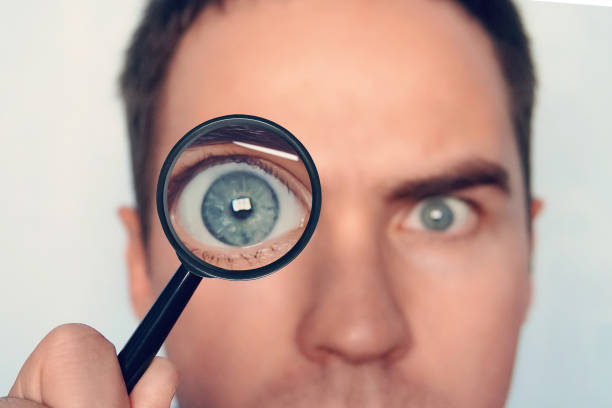 close up of man's face with the loupe close to one eye on white background. view to round human eye through the magnifiying glass. curious researcher. looking through magnifier intently. eye focus. - narrow stock photos and pictures