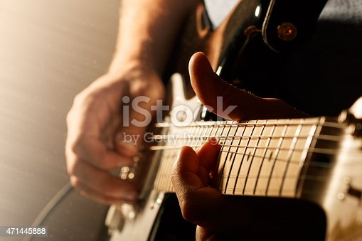 Hands of man playing electric guitar. Bend technique. Low key photo.