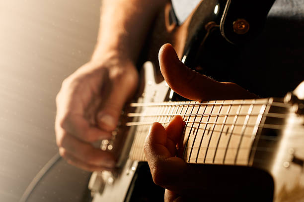 Close up of mans fingers playing electric guitar Hands of man playing electric guitar. Bend technique. Low key photo. guitarist stock pictures, royalty-free photos & images