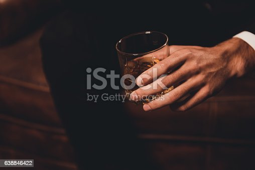 istock Close up of man's hand holding class of whiskey 638846422