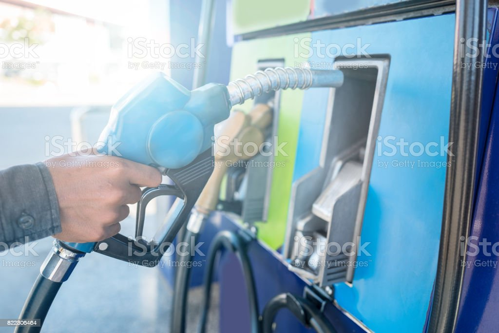 Close up of man's hand holding fuel pump and refueling car in Gas station stock photo