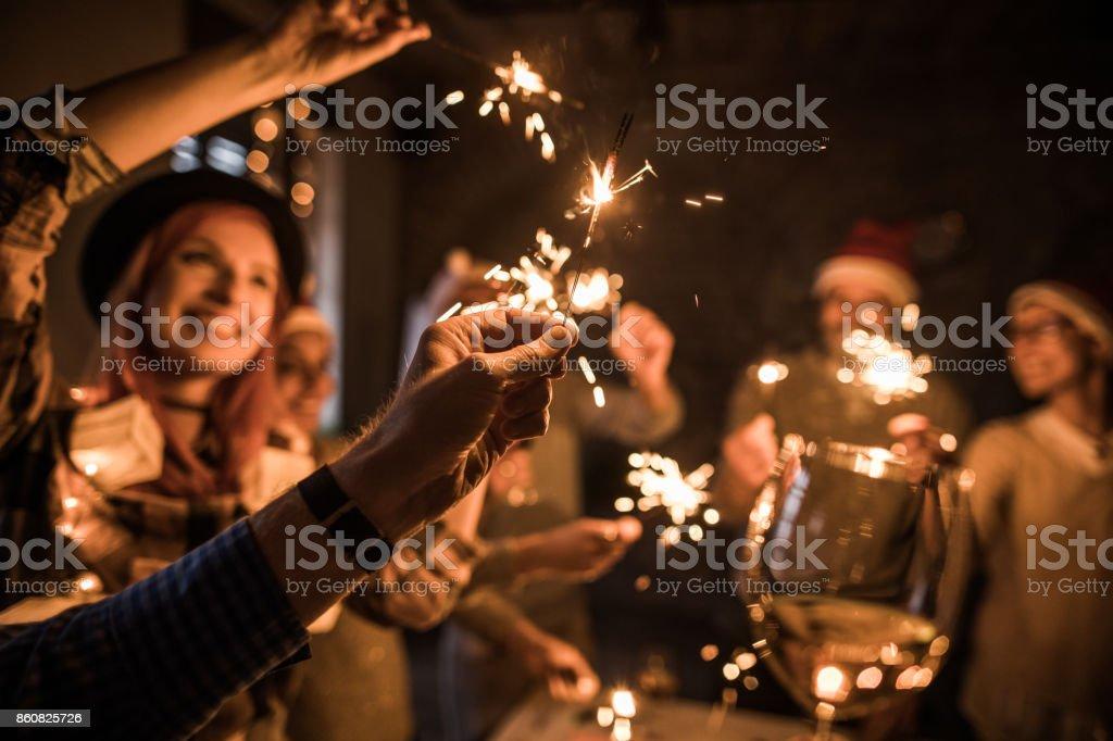 彼の友人とパーティーの最中に線香花火を持っている男の手のクローズ アップ。 ストックフォト
