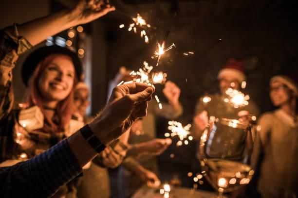 彼の友人とパーティーの最中に線香花火を持っている男の手のクローズ アップ。 - 社内パーティ ストックフォトと画像
