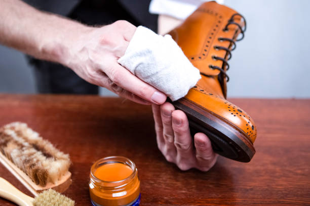 Close Up of Mans Hands Cleaning Luxury Calf Leather Brogues with Special Cloth. Horizontal image Orientation