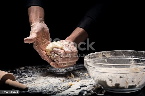 istock Close up of mans hands cooking bakery on black background 624926474