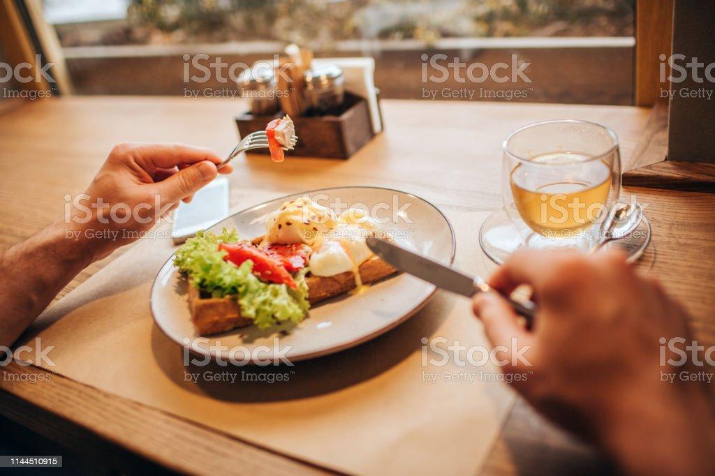 Närbild av mannens händer håller gaffel och kniv. Det finns en tallrik med läckra våffla med grönsaker och en kopp te. Bordet står framför fönstret. - Royaltyfri Aperitif - Måltid Bildbanksbilder