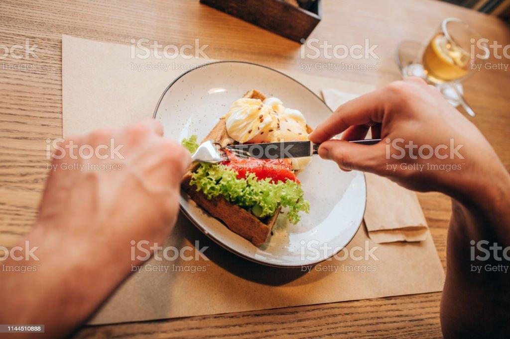 Närbild av mannens händer hålla gaffel och knofe och skär skålen i två delar. Det finns en kopp te på höger sida från mål tiden. - Royaltyfri Aperitif - Måltid Bildbanksbilder