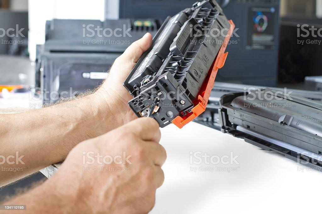 Close up of man's hands repairing toner cartridge royalty-free stock photo