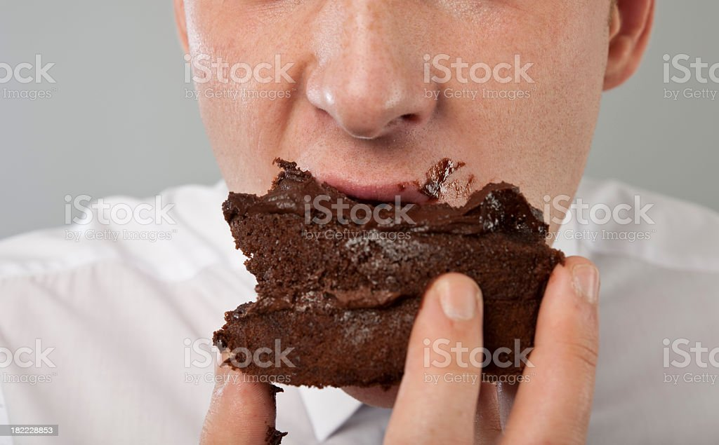 close up of mans mouth eating chocolate cake stock photo