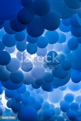 istock Close up of many blue balloons floating in a row 635973492