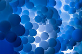 Close up abstract image of hundreds of balloons - most of them different shades of blue and grey and brown - floating in a row. They are backlit, producing an interesting atmosphere. Horizontal colour image with room for copy space.