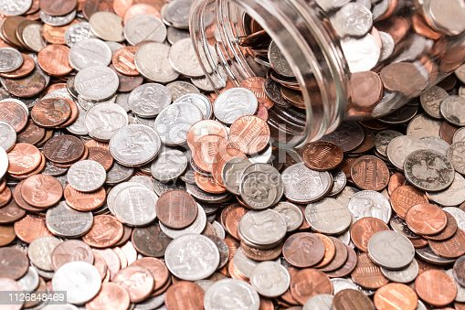 istock Close up of many different type of coins with jar 1126848469