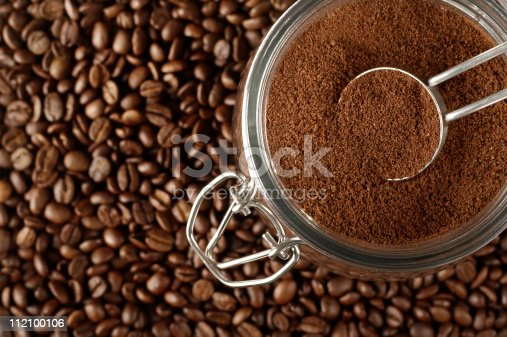 Ground coffee in jar on coffee beans.