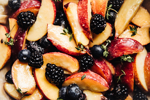 Tasty and fresh marinated nectarine, blueberries and blackberres with pieces of thyme