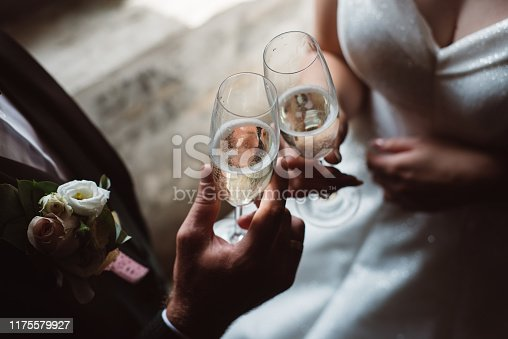Close up of married couple toasting champagne glasses at wedding party. Hands bride and groom clinking glasses at wedding reception.