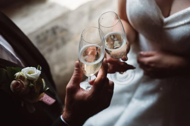 nahaufnahme des ehepaares toasten champagner gläser auf hochzeitsfeier. hände braut und bräutigam klinken gläser bei hochzeitsempfang. - schaumwein fotos stock-fotos und bilder