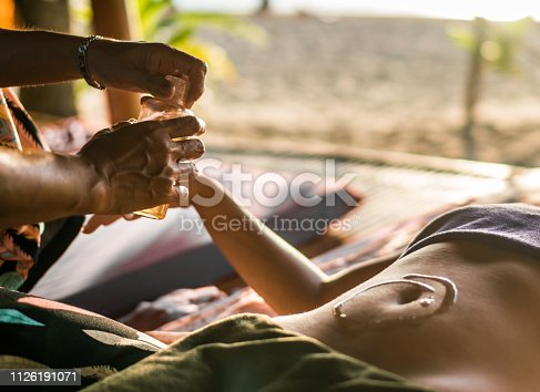 Close up of unrecognizable therapist giving massage to her customer with aromatherapy oil.