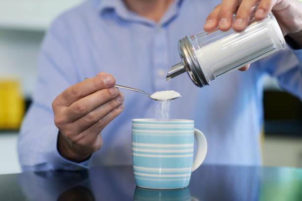 집에서 뜨거운 음료에 설탕을 추가 하는 성숙한 남자의 클로즈업 - 설탕 뉴스 사진 이미지